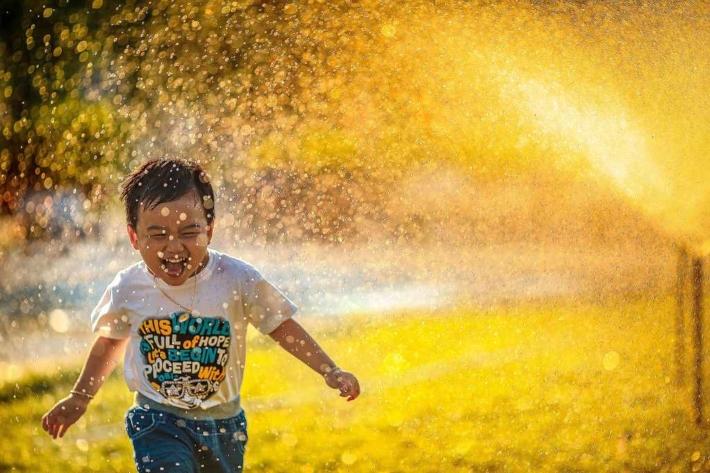 笑顔で噴水を浴びる子供
