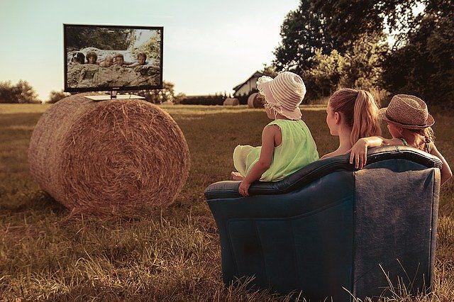 原っぱでソファに座りTVを見ている母娘