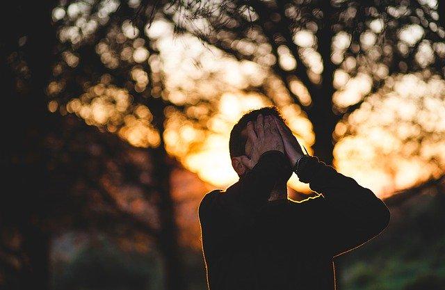 夕日をバックに手で顔を覆っている男性