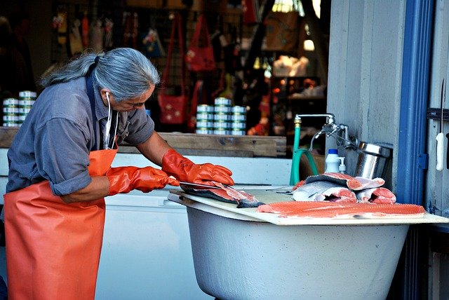 鮭を捌く髪の長い男性