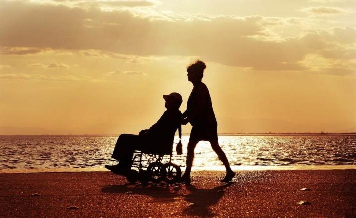 夕日の中 車椅子に座った男性を押す女性