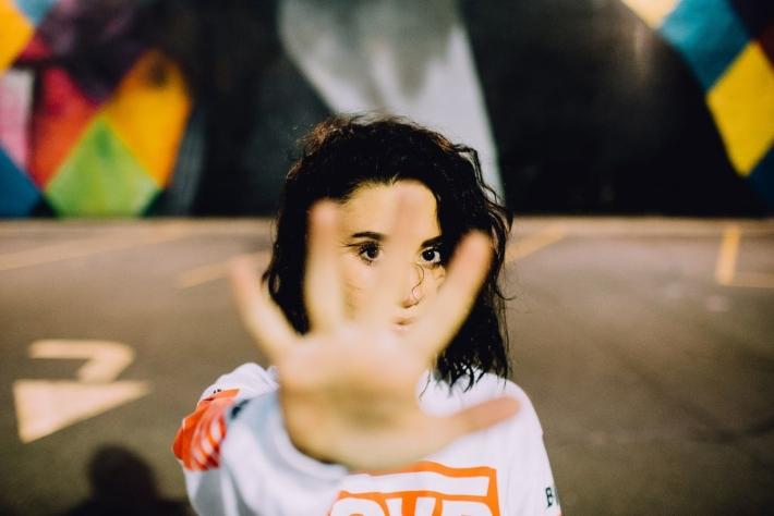 手のひらを目の前にかざしている女性