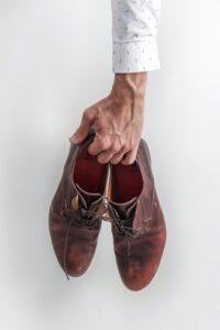 靴を持つ男性の手