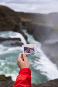 崖で写真をもつ女性の手
