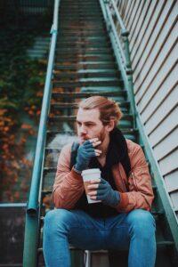 階段でコーヒーを飲みながらタバコを吸う男性